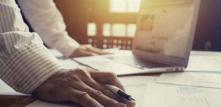 Arbeitende Hände mit Stift, Papier und Notebook